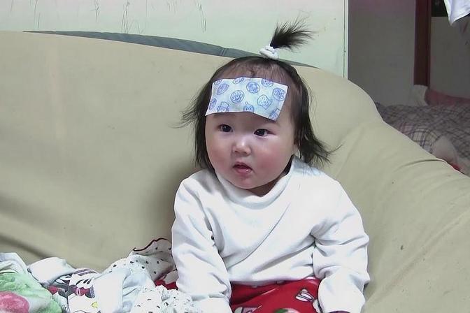 肉嘟嘟的小宝宝发烧了,额头上贴着一块退热贴,小模样真心疼
