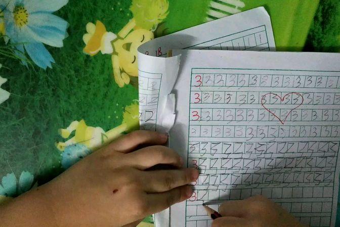 4岁宝宝努力学写字,最上面三行是妈妈握手写的。